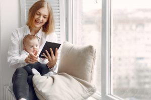 Beautiful woman with child. Woman in a white shirt. Family on a windowsill use the tablet.